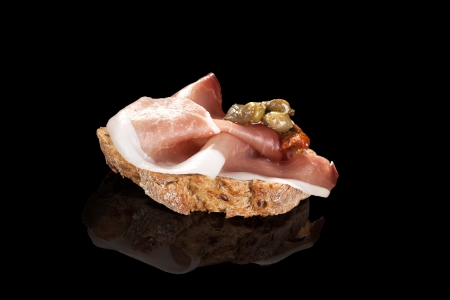 ciabatta: Bread slice with prosciutto ham, capers and dry tomatoes. Culinary canape isolated on black . Fine dining.
