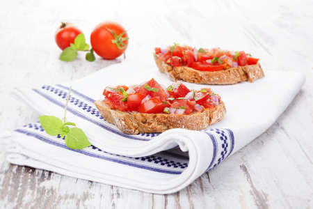 stile country: Delicious bruschetta con pomodoro fresco e erbe su bianco di legno. Mangiare culinario, in stile rustico. Archivio Fotografico