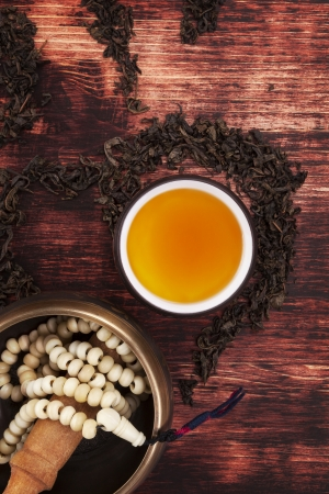 Traditional tea ritual. Tea in cup, dry tea crop forming the ohm symbol, tibetan singing bowl with buddhist necklace on textured brown wooden background, top view. Harmony, buddhism and spirituality. Stock Photo - 24259888