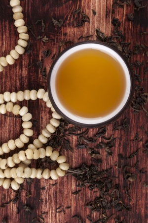 Traditional asian tea ritual. Dry green tea crop, hot tea in cup and buddhist necklace on brown wooden background.   photo