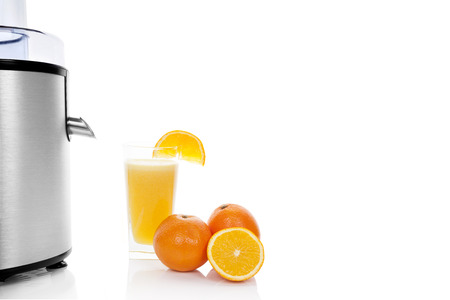 Fresh fruit juicing. Silver juicer, fresh fruit and fresh juice in glass isolated on white . Healthy refreshing summer drink. Stock Photo - 24382519