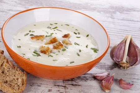 Garlic cream soup in orange bowl on white wooden background. Culinary healthy soup eating, rustic country style.