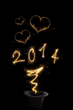 Magical happy new year. Magical fireworks from black top hat forming digits 2014, heart shapes and abstract light lines isolated on black background. Happy new year background. photo
