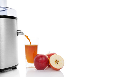 Fresh fruit juicing. Silver juicer, fresh apples and fresh juice in glass isolated on white background. Healthy refreshing summer drink. Stock Photo - 24471691