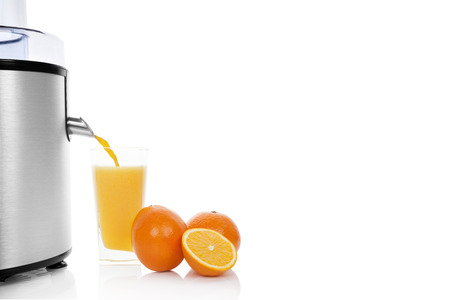 Fresh orange juicing. Silver juicer, ripe oranges and fresh juice in glass isolated on white background with copy space. Healthy refreshing summer drink. Stock Photo - 24471694