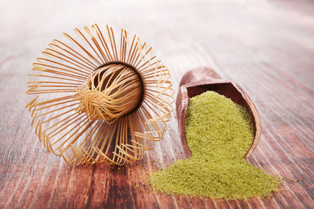 maccha: Green powdered tea on wooden background with wooden scoop Stock Photo