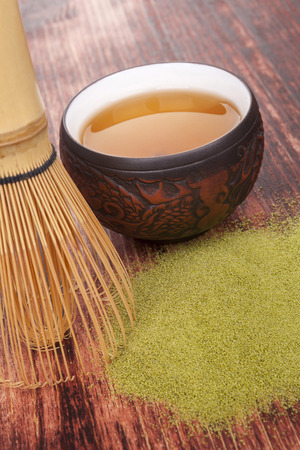 maccha: Traditional green powdered tea matcha on wooden table with bamboo chasen and cup of tea. Tea drinking.