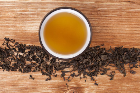 Dry tea leaves and dry green tea in cup on brown wooden table, top view. Healthy alternative medicine. Traditional tea drinking.