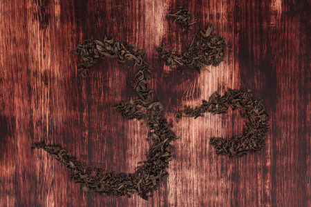 hinduist: Traditional tea ceremony. Buddhist and hinduist symbol ohm. Ohm symbol from green tea on dark wooden table.