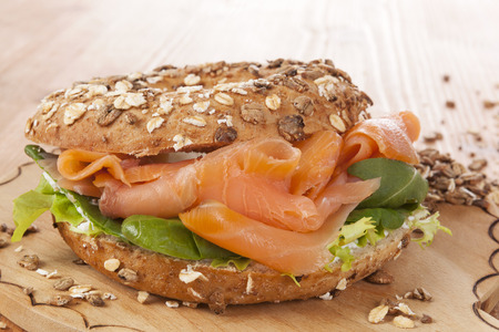 culinary: Whole grain bagel with smoked salmon on wooden background. Culinary healthy bagel eating.