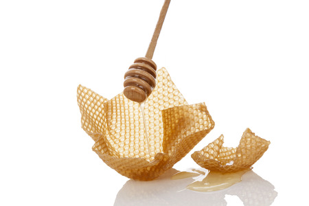 Honey dropping from wooden honey dipper onto honey comb isolated on white background. Organic honey background. photo