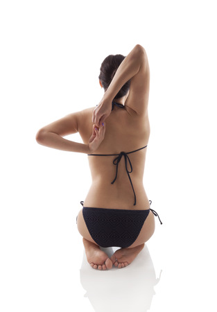 Beautiful girl kneeling and stretching backview. Yoga practice, life balance and wellness. photo