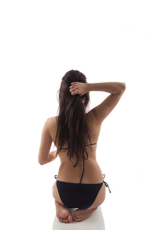Attractive brunette kneeling and touching long brown hair, back view. Yoga practice, balance and wellbeing. photo