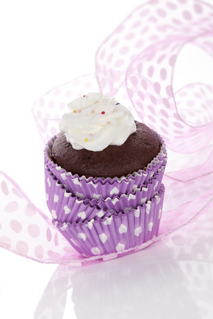 Cupcake. Delicious chocolate cupcake with whipped cream and colorful sprinkles isolated on white background. Contemporary baking concept. photo