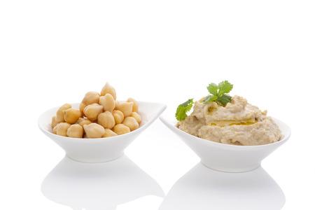 Kikkererwten en hummus in kommen op een witte achtergrond. Culinair-oosterse gerechten.