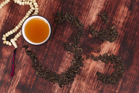 Cup of tea, dry tea leaves forming ohm symbol and buddhist necklace. Traditional tea drinking. Stock Photo - 27106615