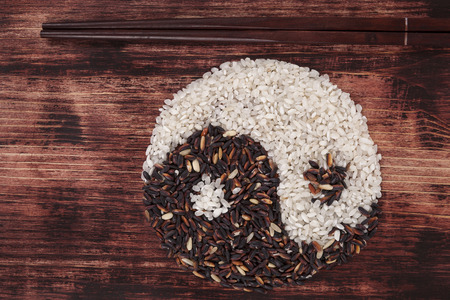 asian culture: White and wild rice shaped as Yin yang symbol with chopsticks on dark wooden background. Asian culture.