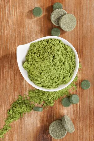 Detox. Chlorella, spirulina and wheatgrass ground and pills on brown wooden background, top view. Alternative medicine. photo