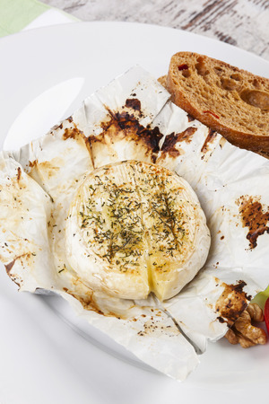 hermelin: Melted unwrapped camembert. Cheese fondue. Culinary vegetarian eating. Stock Photo