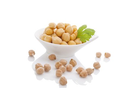 Chickpeas in white bowl isolated on white background with reflection. Healthy legume eating.