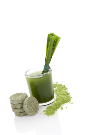 Green food supplement. Spirulina, chlorella and wheatgrass. Effervescent pills, wheatgrass blades, green juice and ground powder isolated on white background. Healthy lifestyle. photo