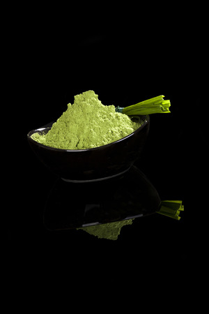 Green powder in bowl and grass blades isolated on black background. Healthy nutritional supplements. Green superfood, detox concept.  photo