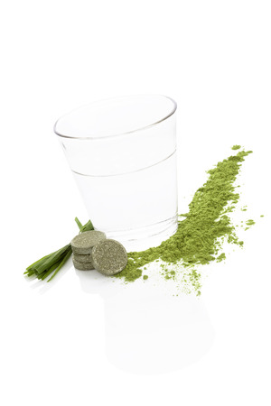 Spirulina; chlorella and wheatgrass. Green food supplement. Green effervescent pills; wheatgrass blades and ground powder isolated on white background. Healthy lifestyle. photo
