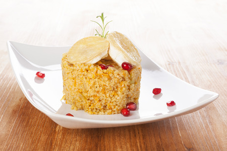 Couscous with goat cheese on plate decorated with pomegranate. Culinary vegetarian eating.  photo