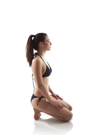 Girl in bikini kneeling isolated on white background. Relax after yoga exercise. Sports, fitness and healthy living.  photo