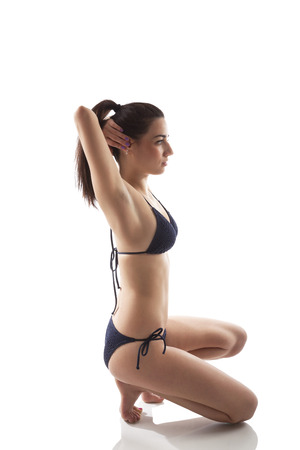 Stretching after sports. Beautiful girl in bikini stretching after sports. Caucasian brunette with long brown hair, isolated on white background. Healthy living. photo