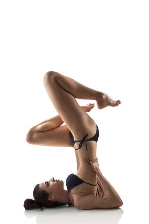 Beautiful girl in bikini doing shoulder stand. Caucasian woman doing yoga. Sarvangasana asana. photo