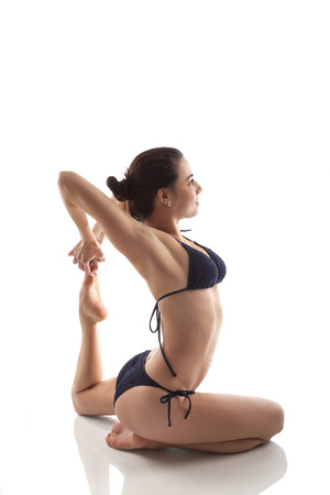 Beautiful girl in her 20s in bikini stretching over white background. Yoga, healthy lifestyle and stretching. photo