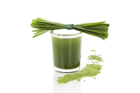 Wheatgrass powder, grass blades and green juice isolated  Stock Photo