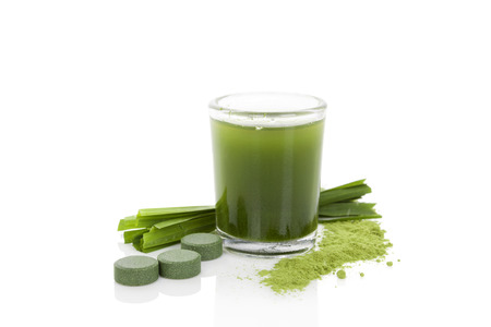 Detox. Green dietary supplement spirulina, chlorella and wheatgrass pills, grass blades and green juice isolated photo