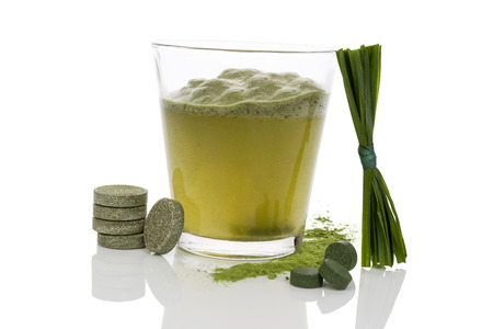 Green drink with green chlorela and spirulina effervescent tablet dissolving in water and blades of grass isolated on white background. Healthy life. photo