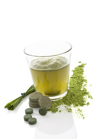 Green juice. Dietary supplements, spirulina, chlorella, wheatgrass tablets, pills and blades of grass isolated on white background. Healthy living, alternative medicine. photo