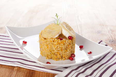 Delicious couscous with goat cheese on wooden background. Traditional culinary eating. photo