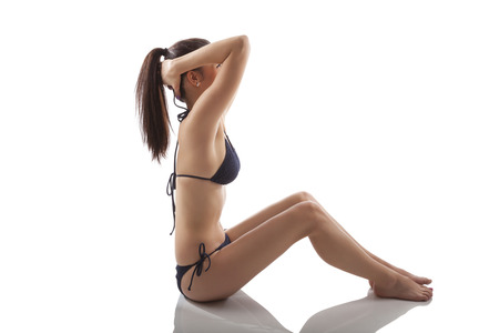 Sports and Fitness. Attractive sexy woman in bikini sitting and stretching isolated on white background.  photo