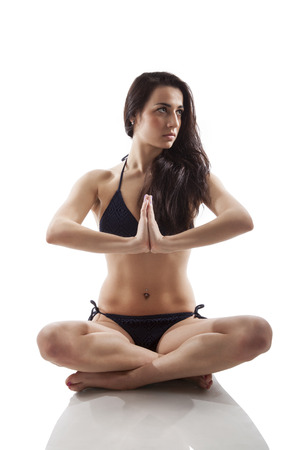 Attractive young woman in lotus position meditating isolated on white background. Balance and piece. photo