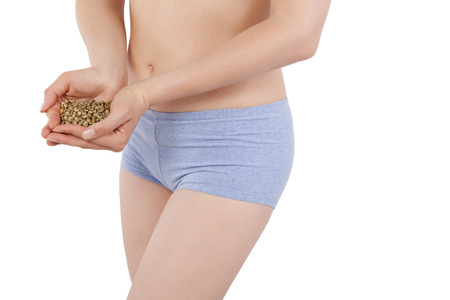 Beautiful skinny woman in panties holding green coffee beans isolated on white background. Weight loss, detox and diet. photo
