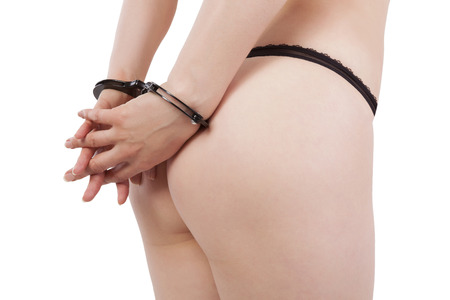Hot young woman in black panties and handcuffs isolated on white background.  photo