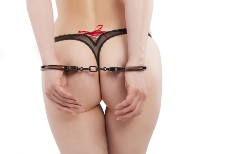 Hot sexy ass in panties and hands with handcuffs backview isolated on white background.  photo