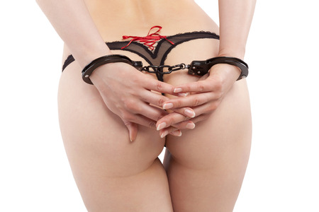 Seductive sexy woman with perfect ass and handcuffs in string tanga isolated on white background.  photo