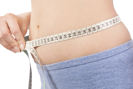 Girl in panties measuring her body with tape measure detail isolaled on white. Belly detail. Weight loss and diet. photo