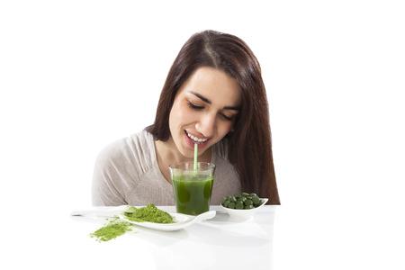 Mooi glimlachend meisje het drinken van groene drankje. Spirulina, chlorella en tarwegras. Gezonde levensstijl, detox.