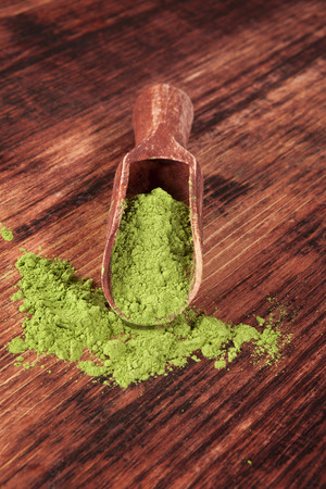 Green food supplement. Wheatgrass ground on brown wooden scoop on brown wooden background. Healthy natural detox.  photo
