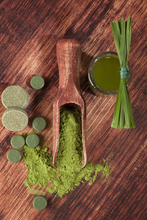Detox. Chlorella, spirulina, wheat grass and barley grass pills, tablets, grass blades and ground powder on wooden background. Healthy lifestyle, alternative medicine.  photo