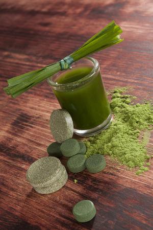 Green drink with green pills and ground powder. Chlorella, spirulina and wheat grass. Detox and alternative medicine.  photo