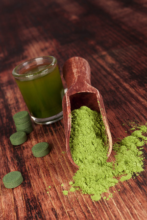 Nutritional supplements chlorella, spirulina and wheat grass on wooden background. Pills, green drink and ground powder. Green superfood. Alternative medicine and detox.  photo