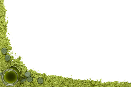 Green food supplements background. Ground powder, green pills and green drink on white background with copy space. Alternative medicine, healthy living. photo